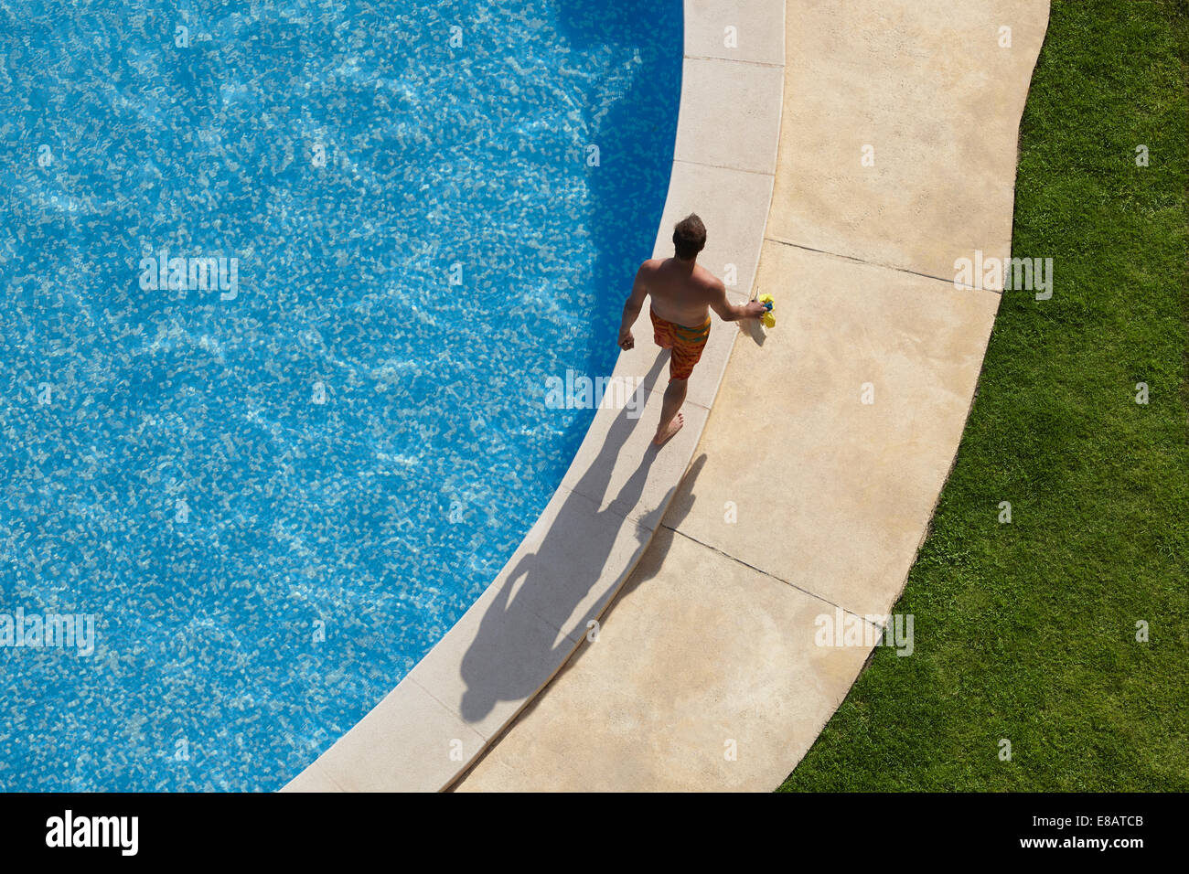 Overhead view of man walking around swimming pool - Stock Image