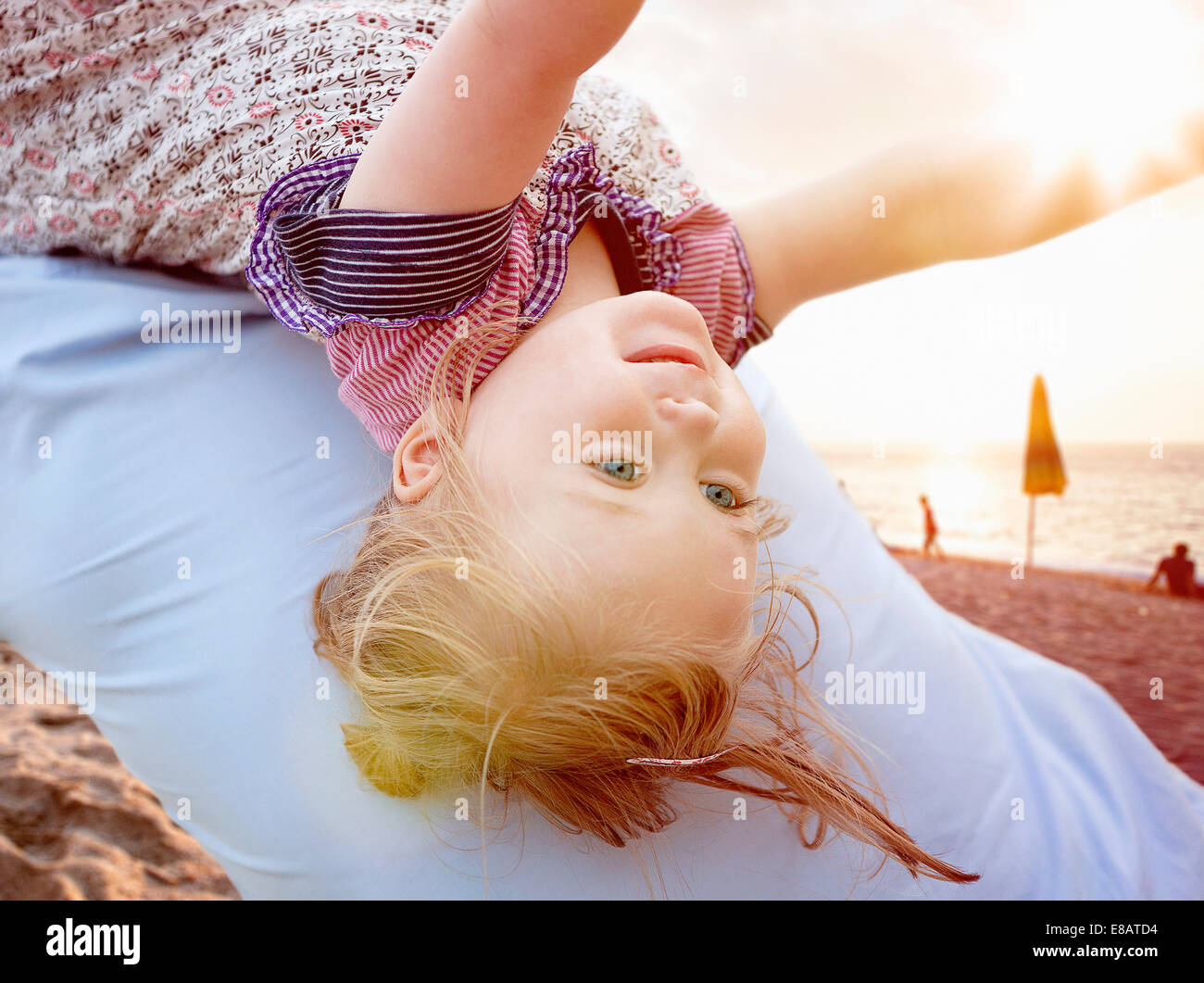 Person carrying young girl on back - Stock Image