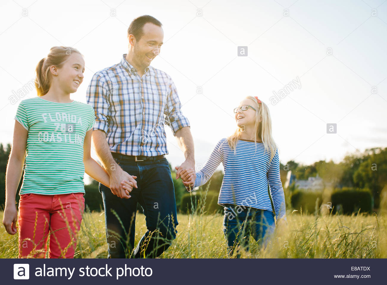 Father on walk with two daughters, holding hands - Stock Image