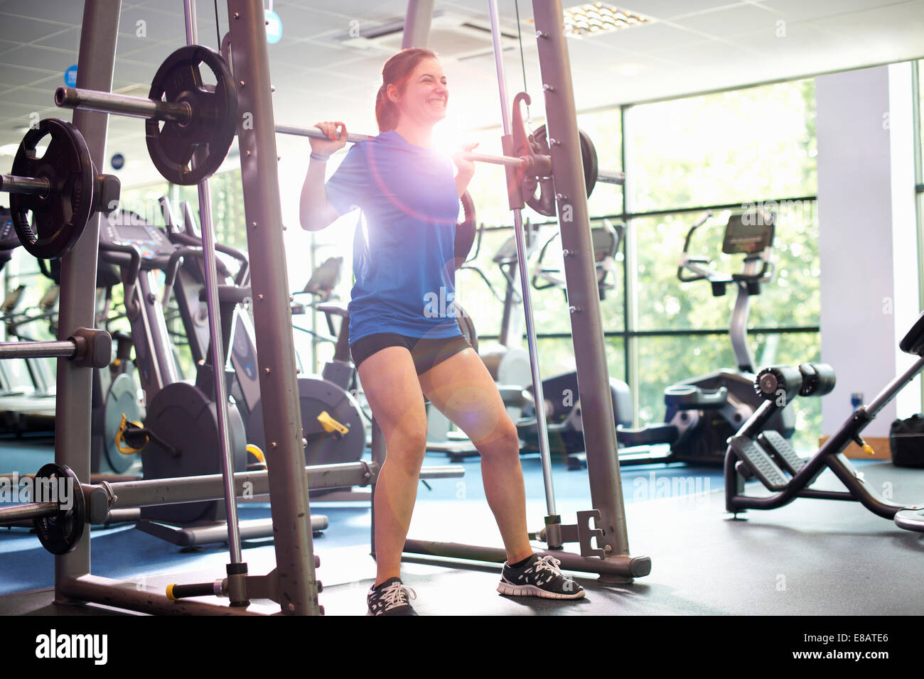Young woman weight lifting with barbell - Stock Image