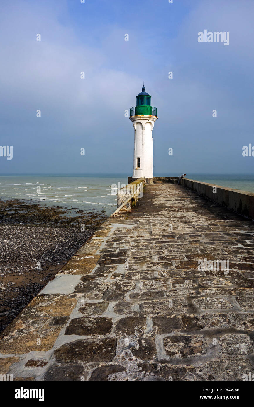 Lighthouse and lonely man looking at sea from pier in the harbour at Saint-Valery-en-Caux, Upper Normandy, France - Stock Image