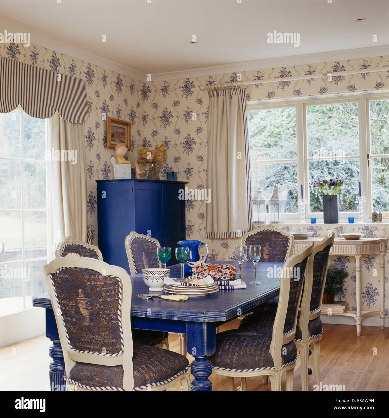 Upholstered White Chairs And Painted Blue Table In Country Dining Room With  Blue+white Patterned Wallpaper