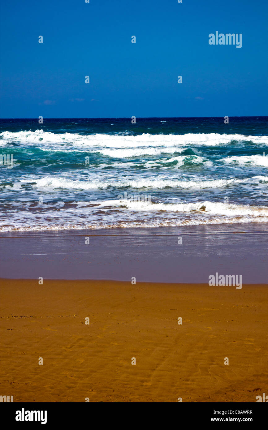 Waves lapping onto a beach - Stock Image