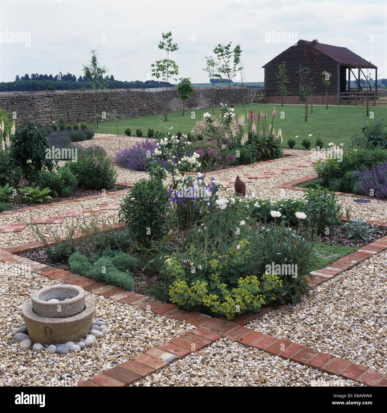 Brick Around Shed With Mulch And Flowers: Flower Beds In Gravel Garden With Brick-paved Edging Stock