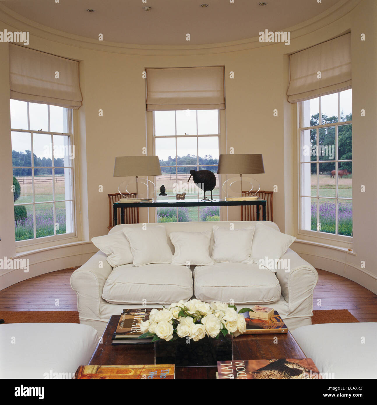 White Sofa In Front Of Large Bay Windows With White Blinds In