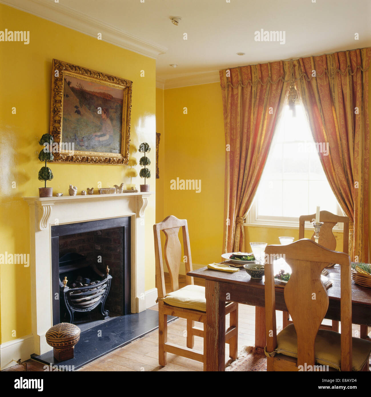 Large Gilt Framed Mirror Above Fireplace In Yellow Dining Room With Full Length Curtains At The Window