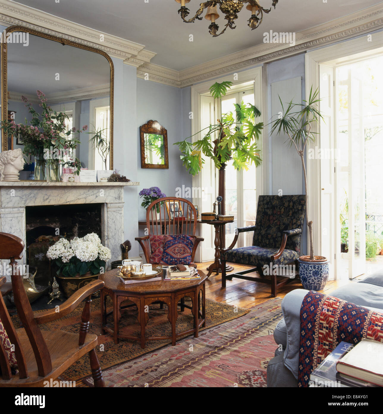 Large Mirror Above Marble Fireplace In Pale Grey Living Room With Green Houseplants