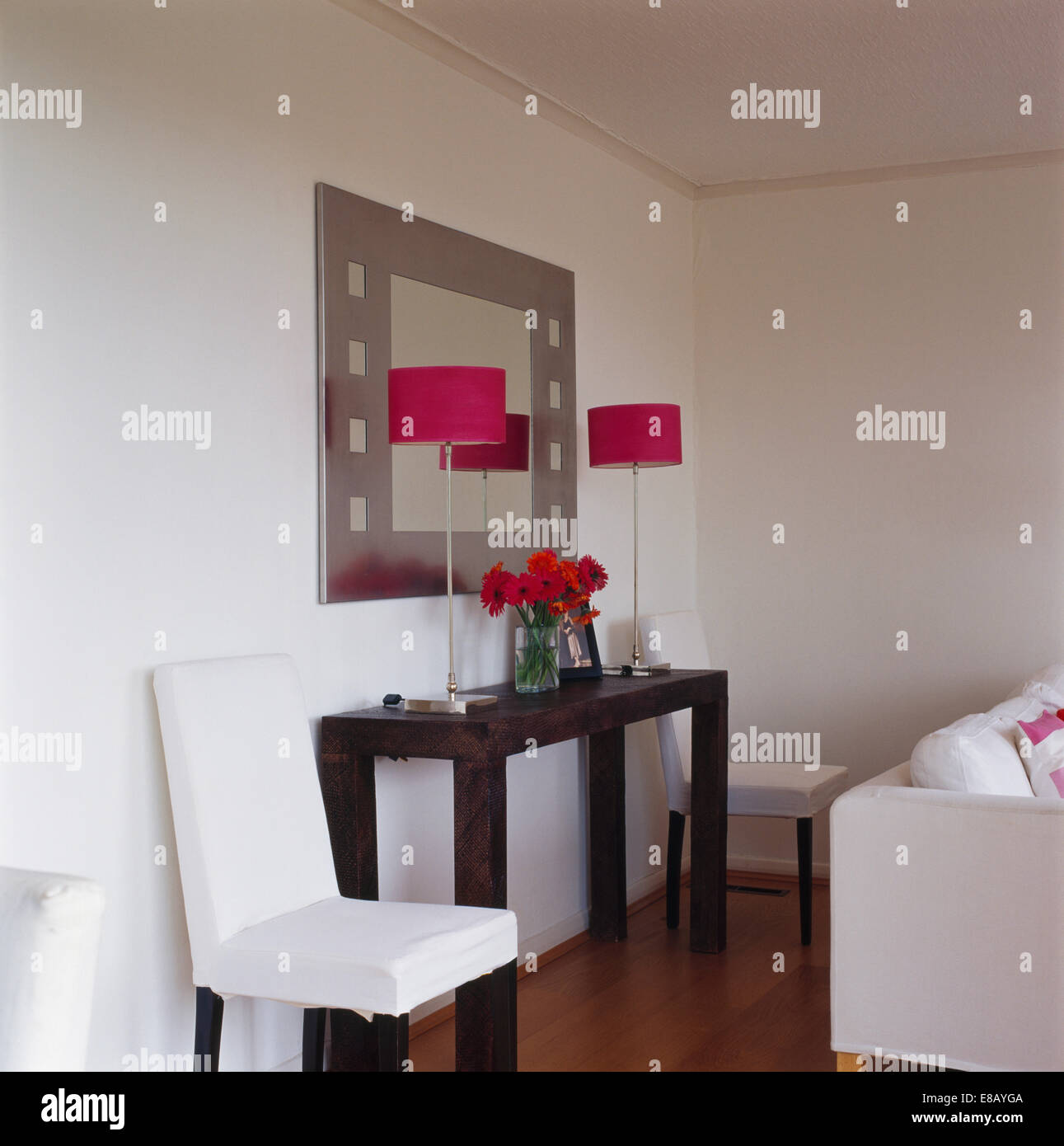 White Loose Covers On Dining Chairs On Either Side Of Console Table With  Red Lamps Below Mirror On Modern Living Room Wall