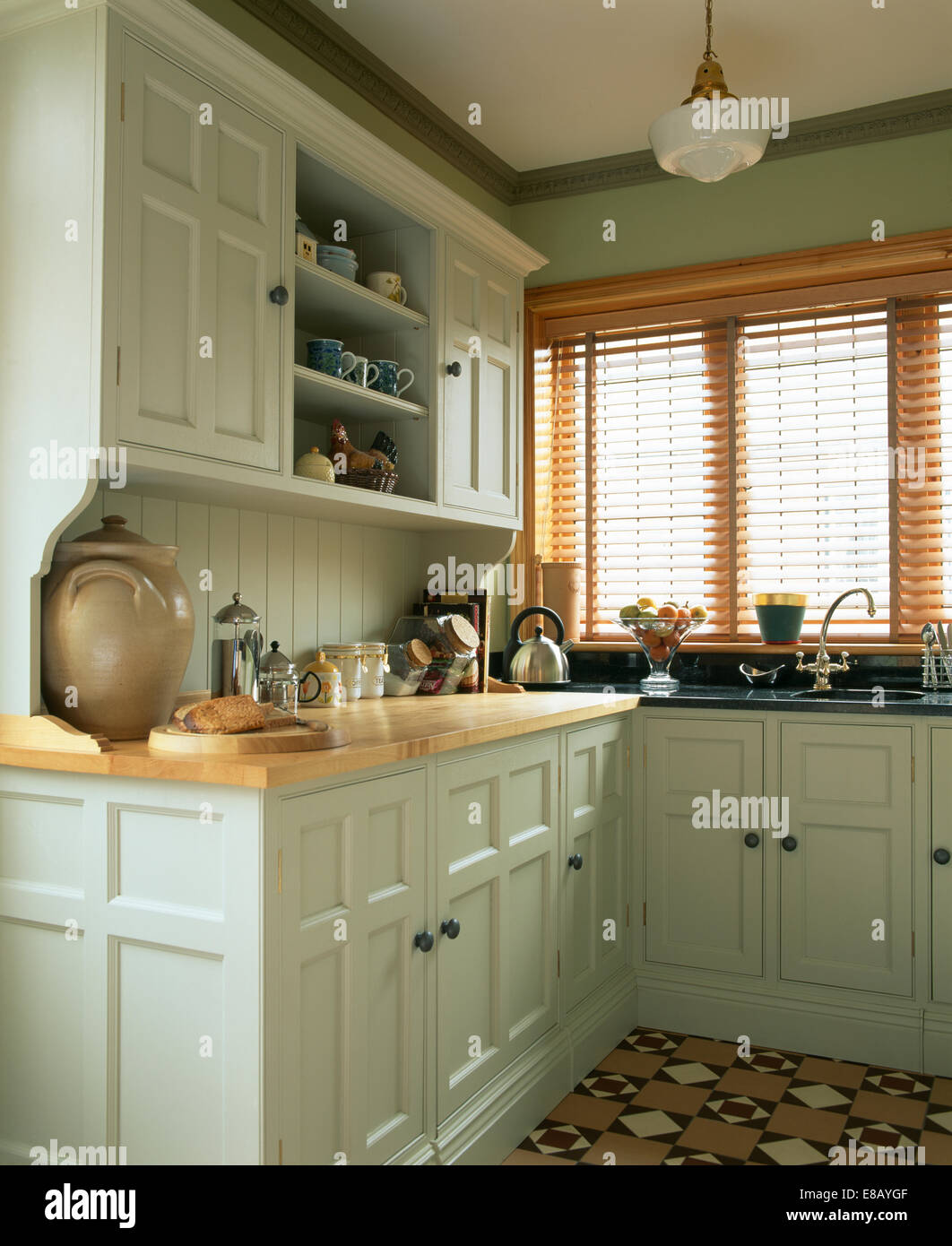 Slatted wooden blind on window in kitchen in traditional ...