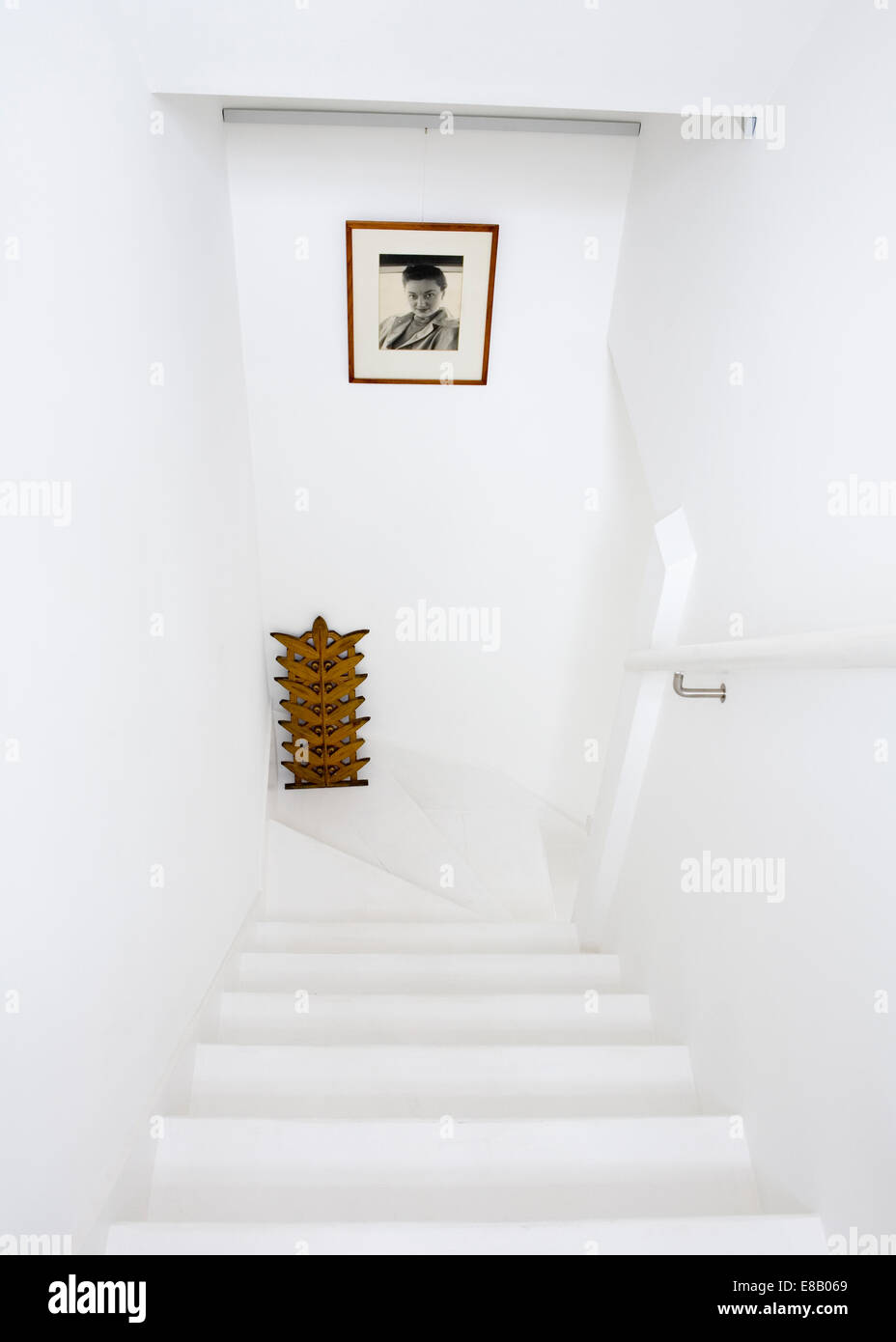 Looking down all white cottage staircase with framed black+white photograph - Stock Image