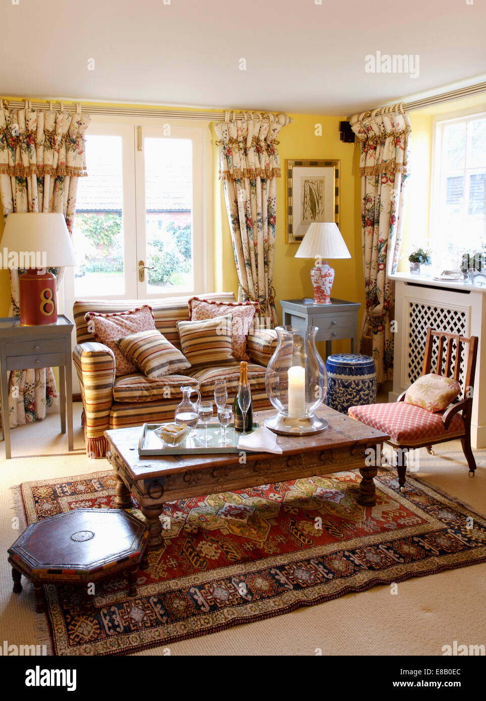Brown striped sofa and floral curtains in yellow living room ...