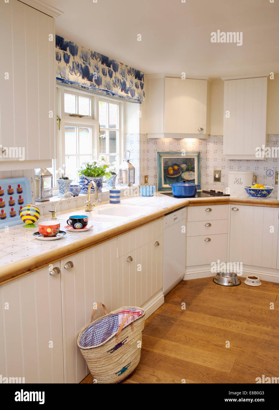 Shopping Basket On Wooden Floor In Cottage Kitchen With Cream Units And  Blue And White Blind