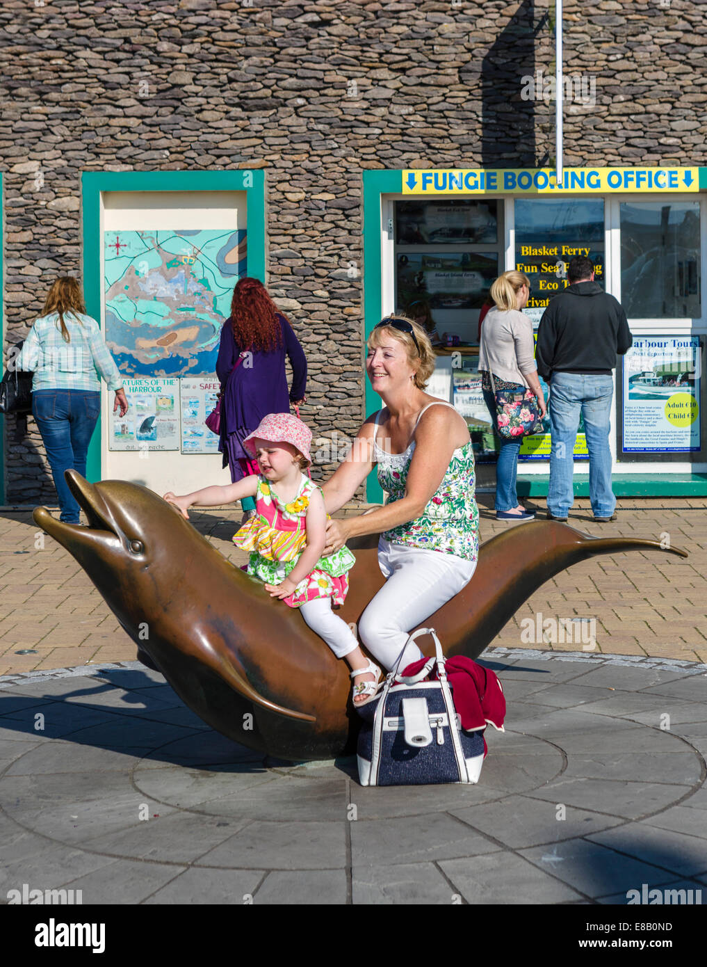 Mother and young daughter posing for photo on Statue of Fungie the Dingle Dolphin, Dingle, County Kerry, Republic - Stock Image