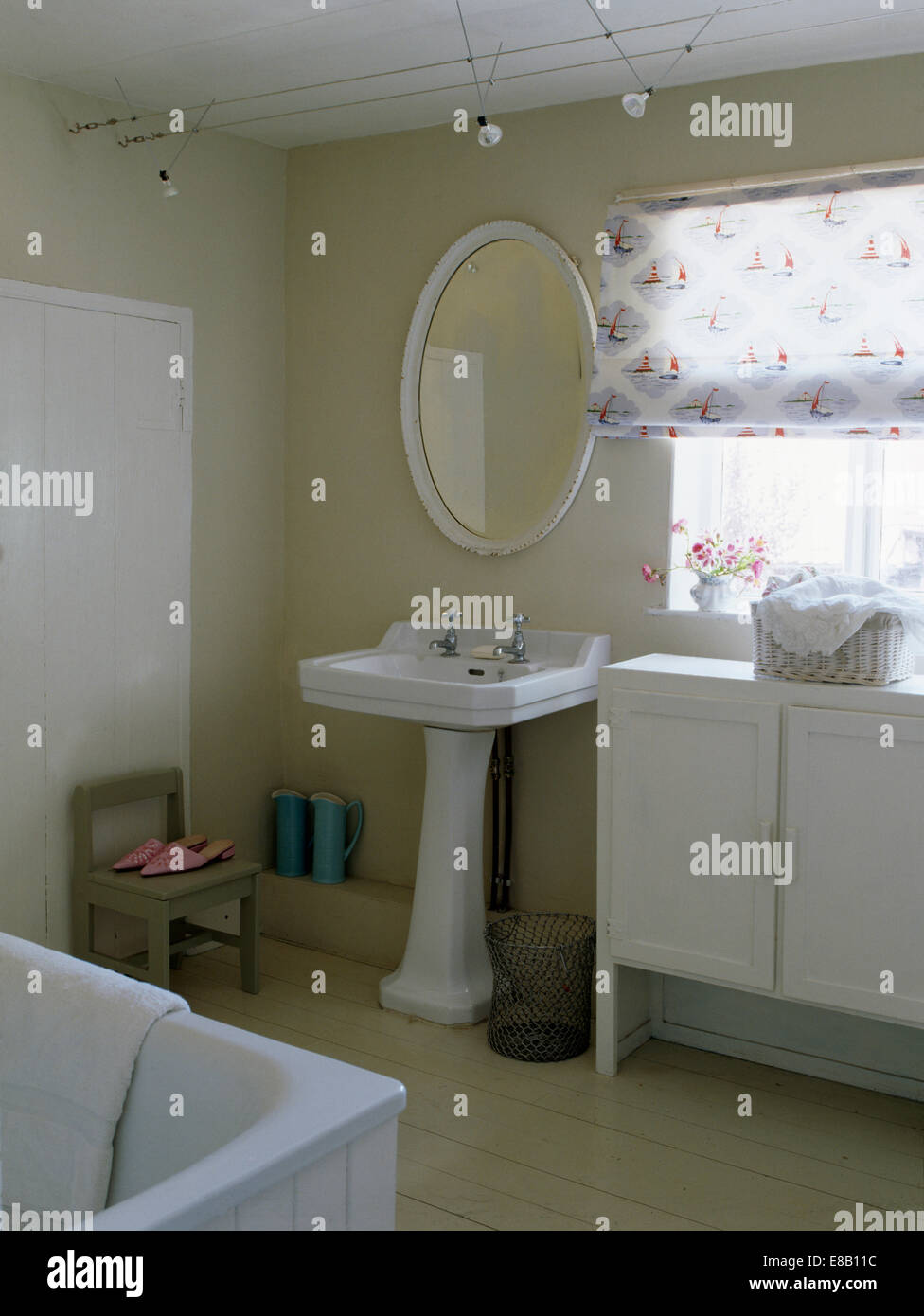 Oval Mirror Above White Pedestal Basin In Country Bathroom With Patterned  White Blind On Window Above Painted Cupboard