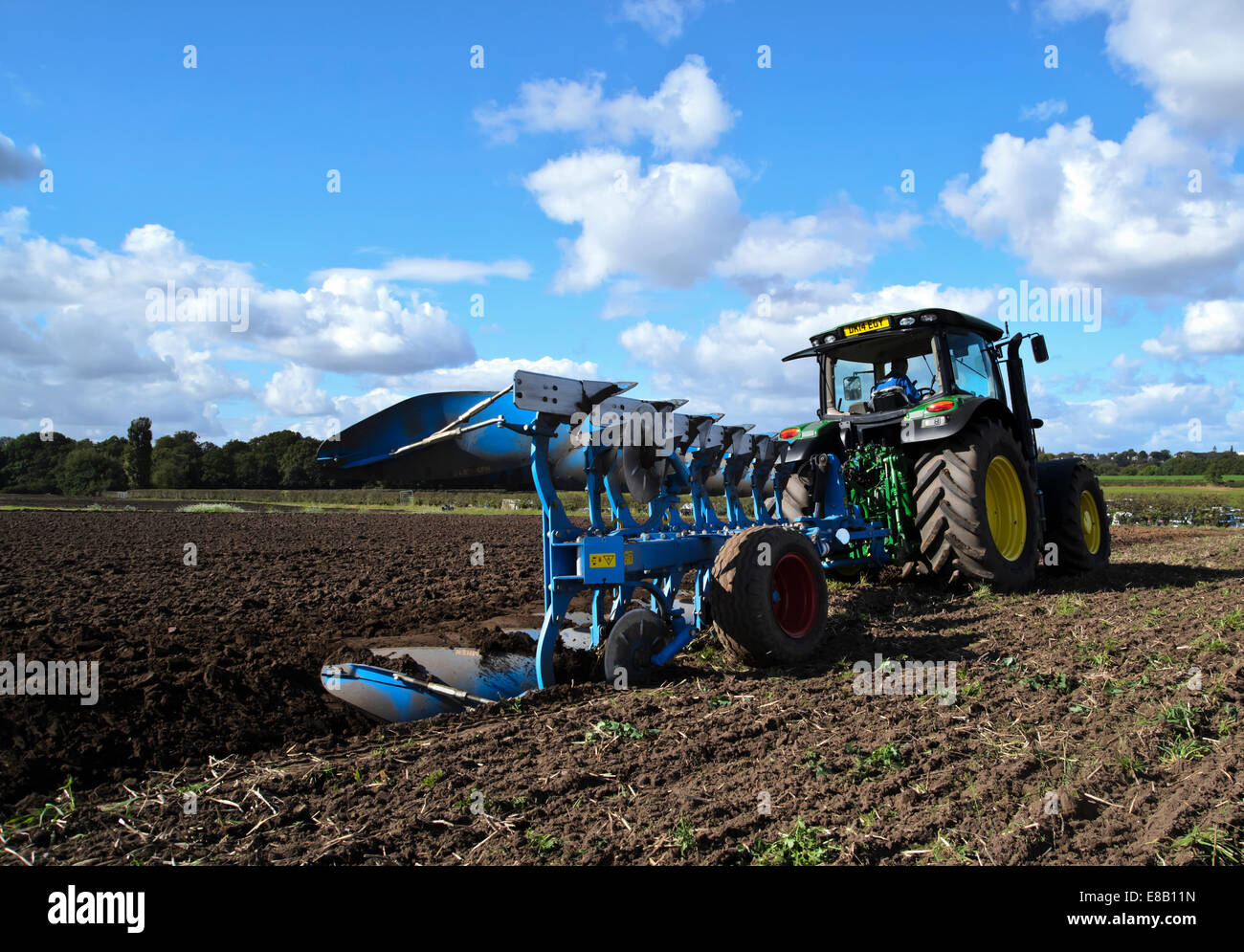 big 'jonh deeere' tractor ploughing plowing with wheeled six furrow reversible plough plow - Stock Image