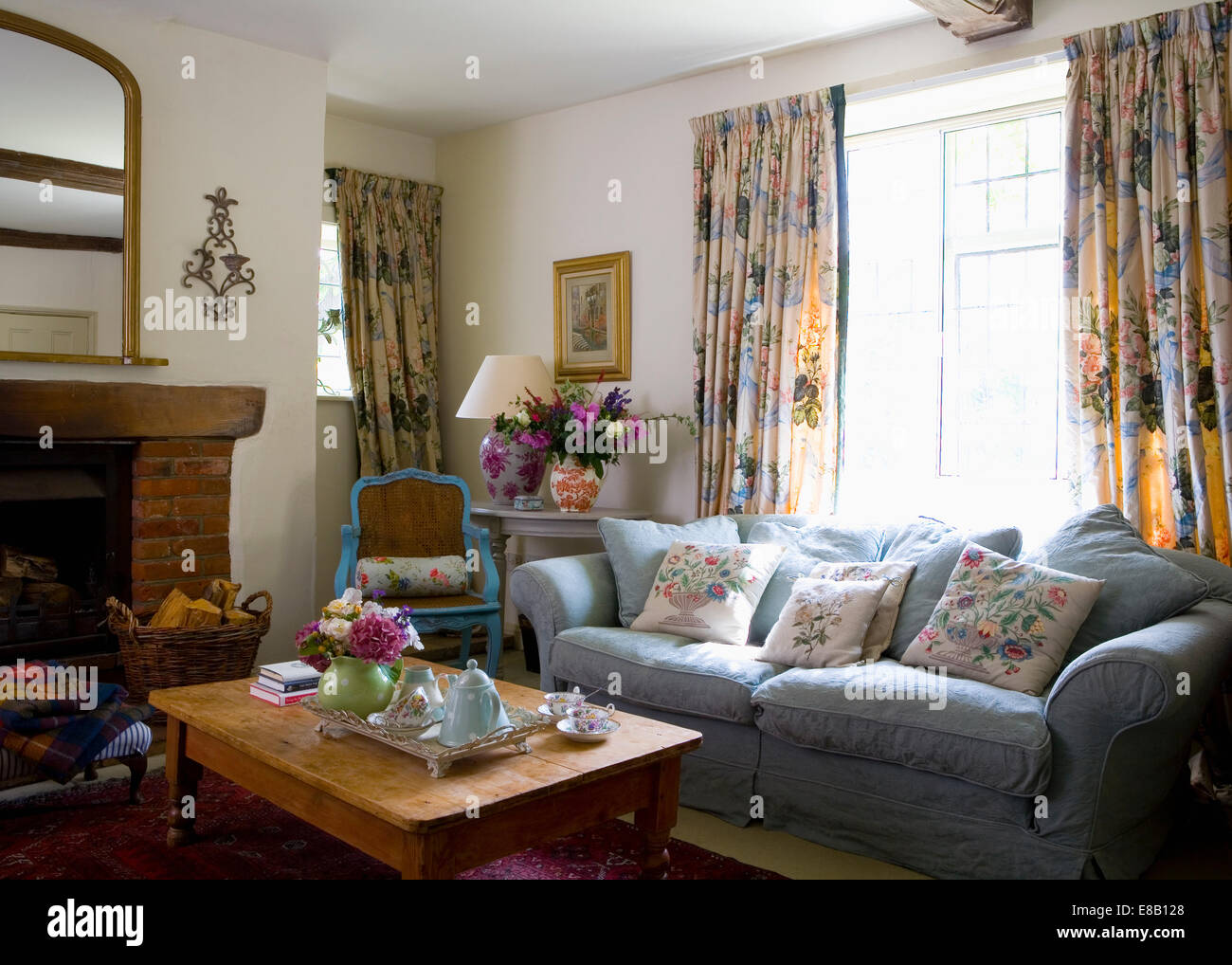 Blue sofa in front of window with floral curtains in country