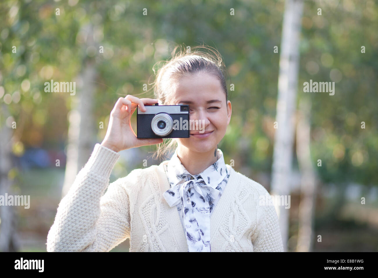 Hipster girl shooting on film camera outdoor - Stock Image