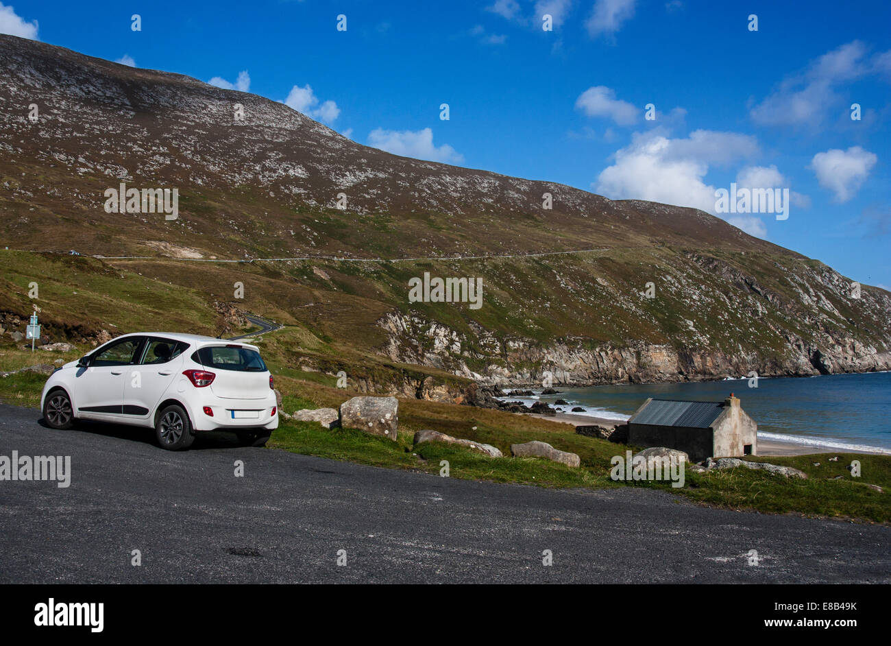 A rental car sits at Keem Strand, Achill, Mayo, Ireland, at the end of the stunning coastal drive, part of the Wild - Stock Image