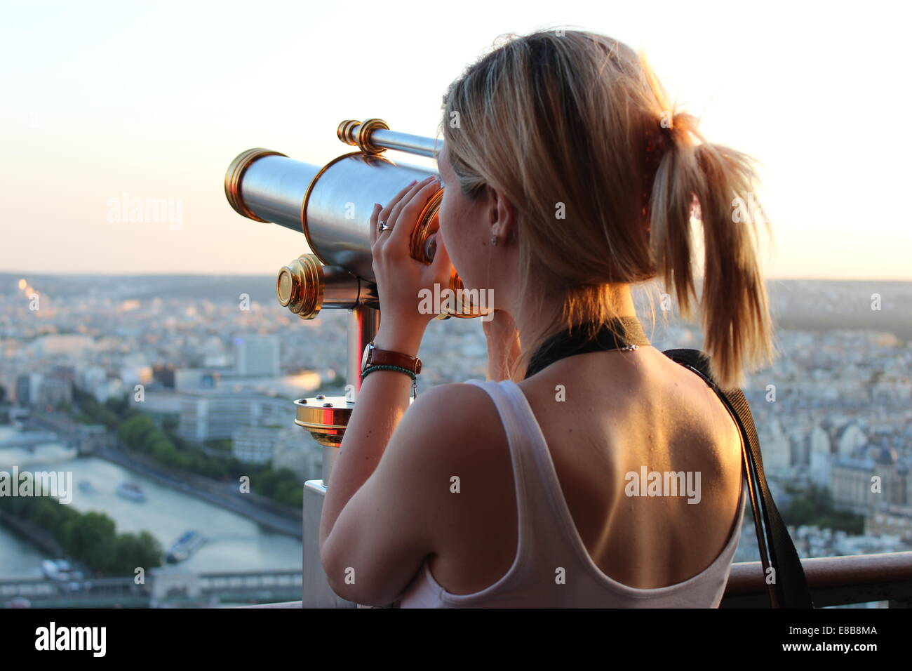 Blonde girl looking at the view from the Eiffel Tower - Stock Image