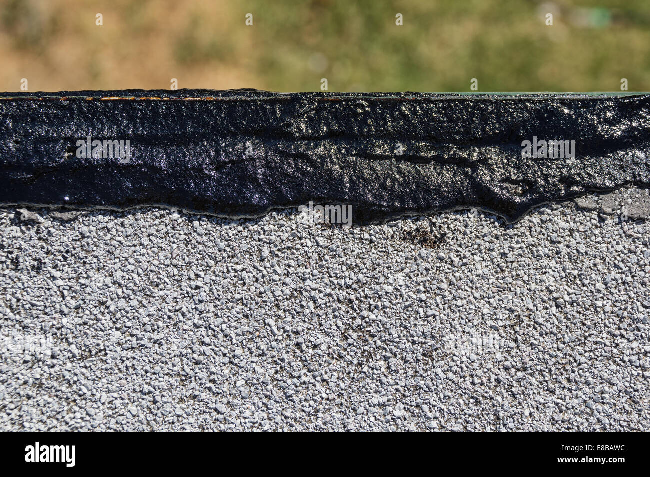 fresh tar roof wet patch along the edge of a flat roof - Stock Image