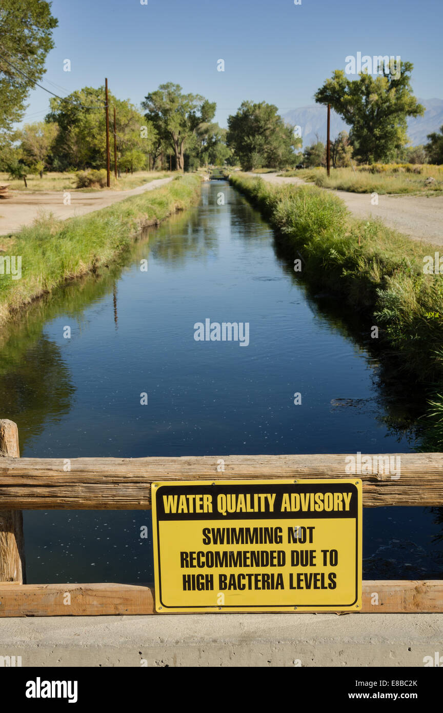 water quality advisory sign warning against swimming in an irrigation canal due to high bacteria levels - Stock Image