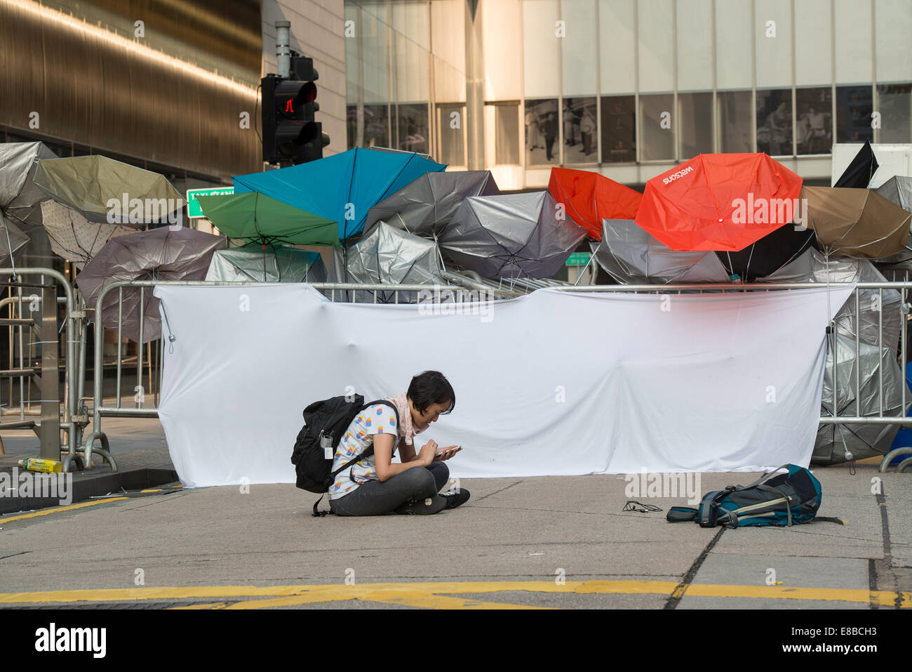 Making sure the outer barriers are watched, this lone protester spends time on her smartphone keeping in touch with - Stock Image