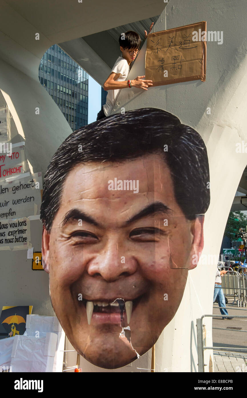 Student protester hangs another sign on the underpass next to a massive banner of CY Leung, Hong Kong's Chief - Stock Image