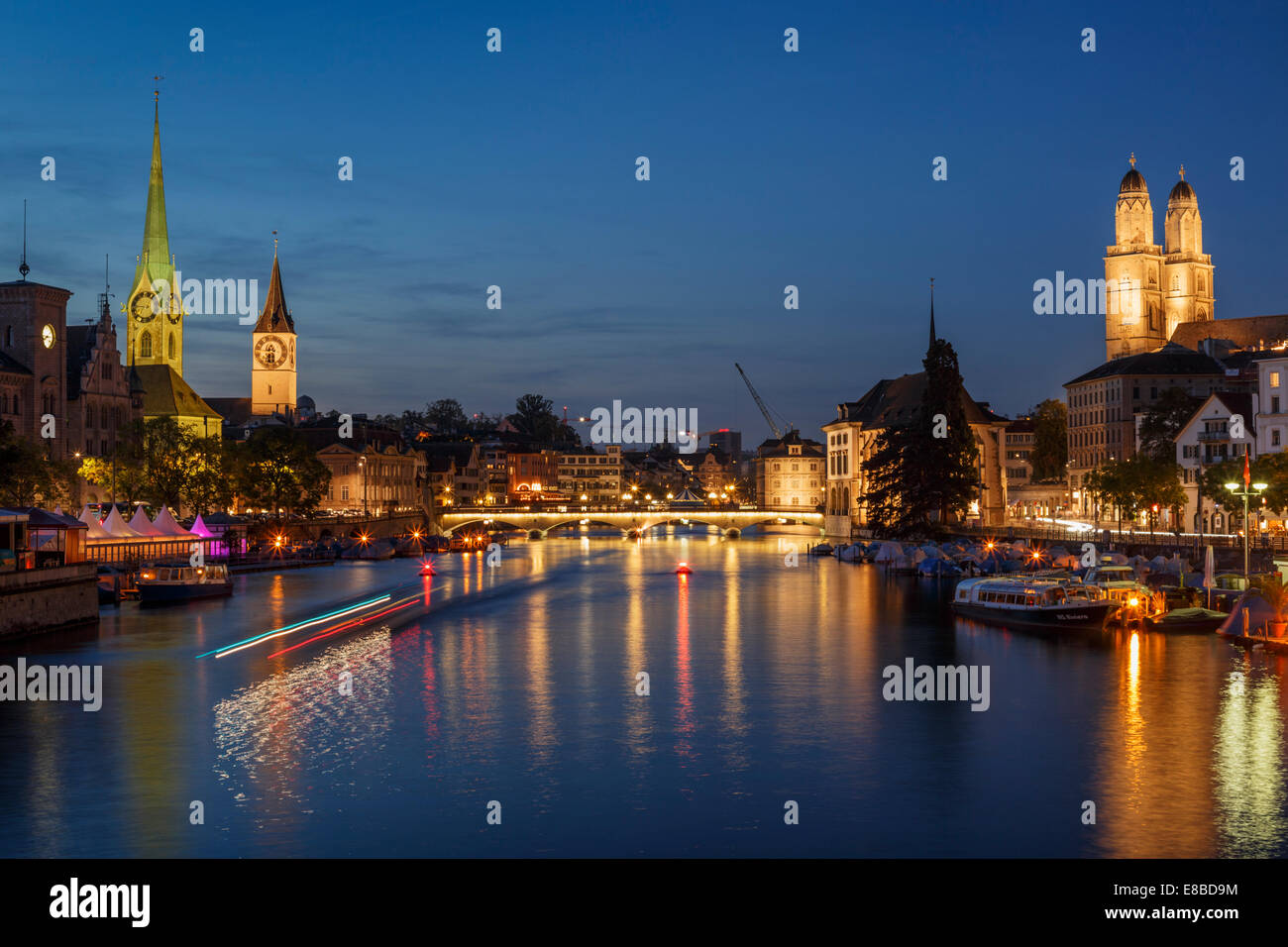 The old town of Zurich at night with the river Limmat with light trails of a waterbus, Switzerland. Stock Photo