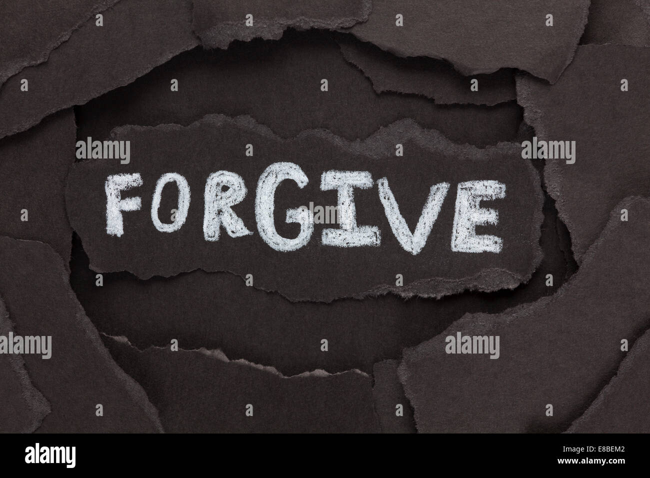 Forgive. Torn pieces of black paper and the word 'Forgive'. Close-up. - Stock Image