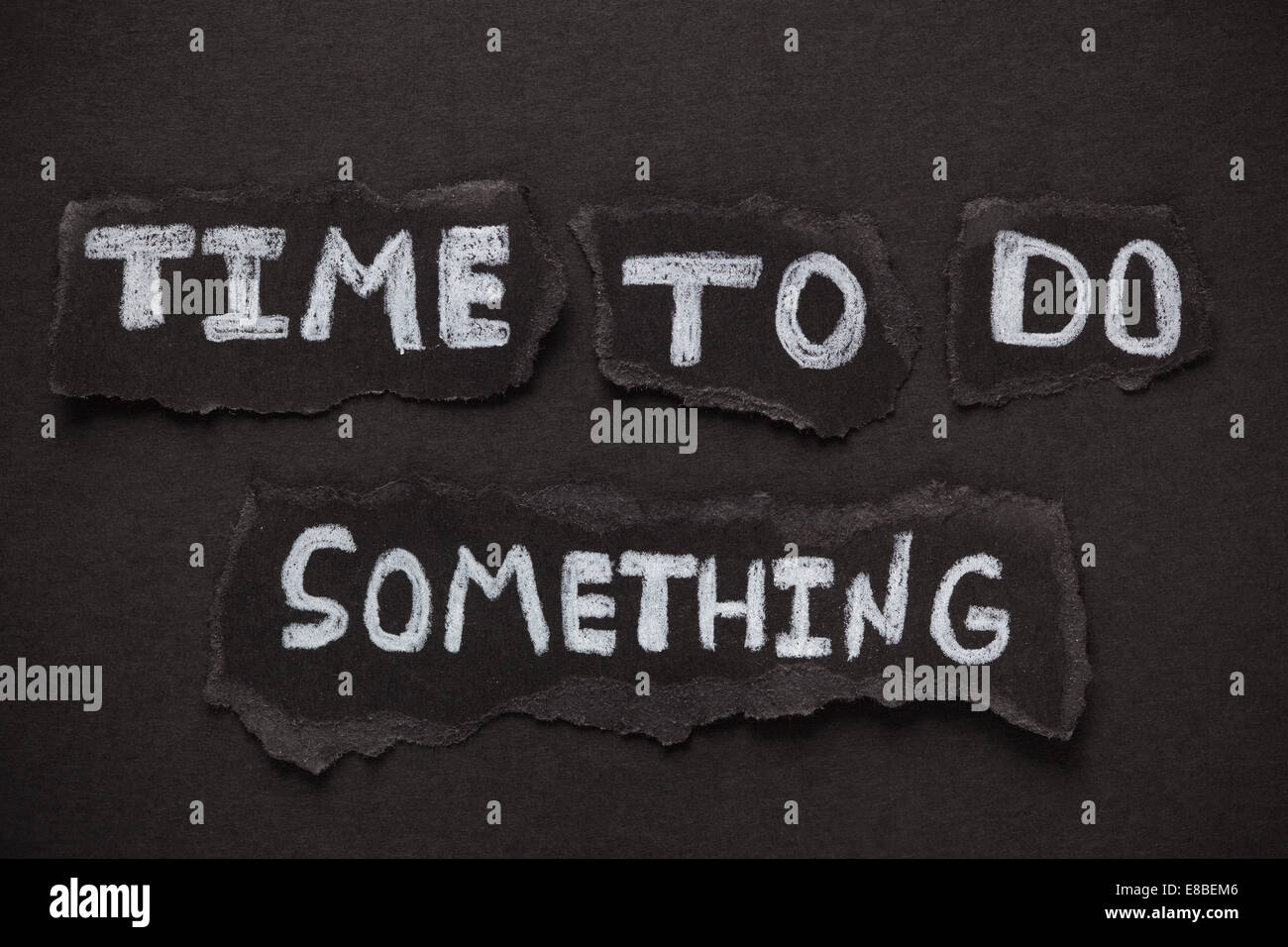 Torn pieces of black paper and words 'Time to do something'. Close-up. - Stock Image