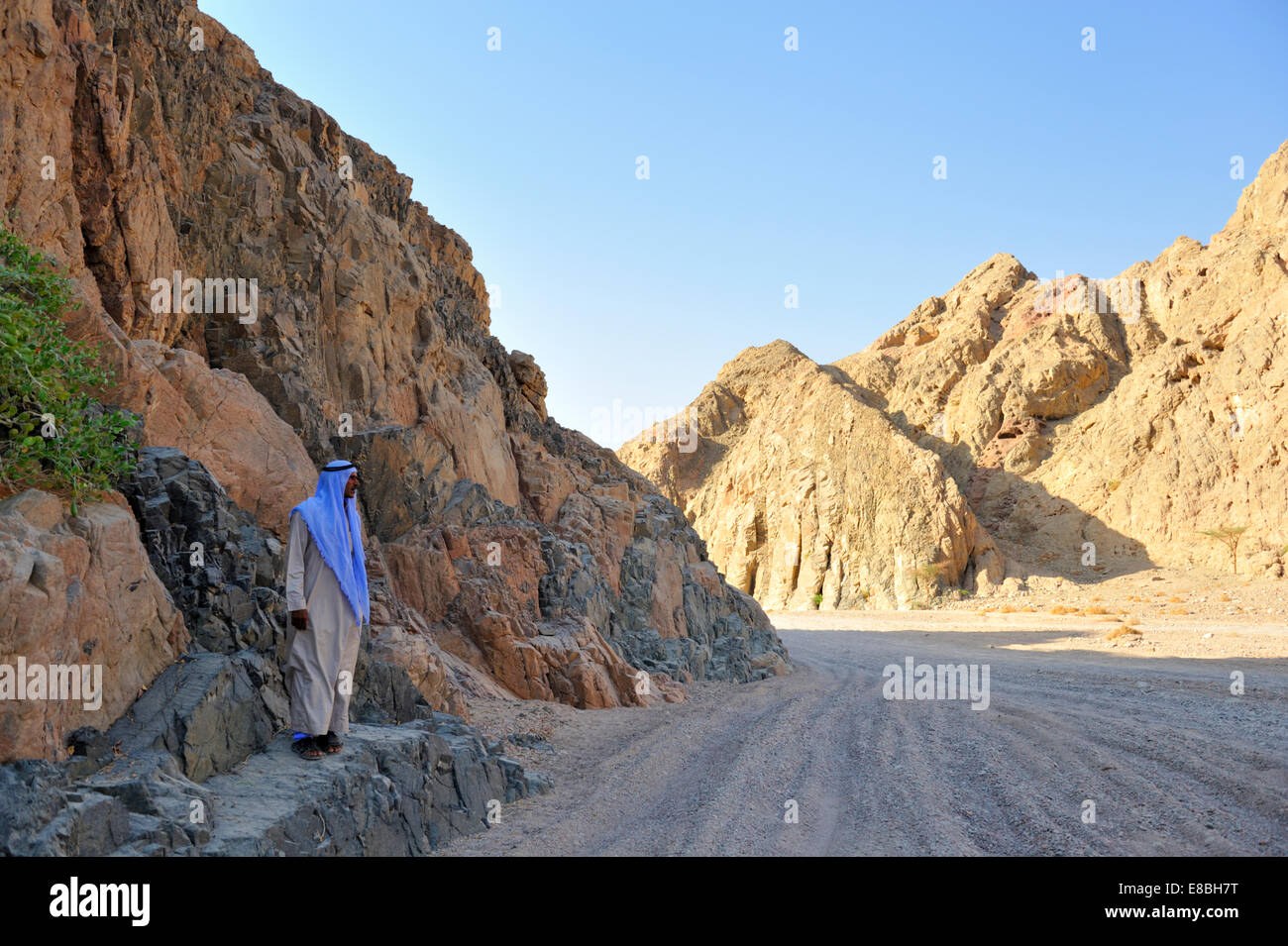 Sinai Peninsula desert track between mountains with Bedouin man in traditional thawb robe and kufeya head ware - Stock Image