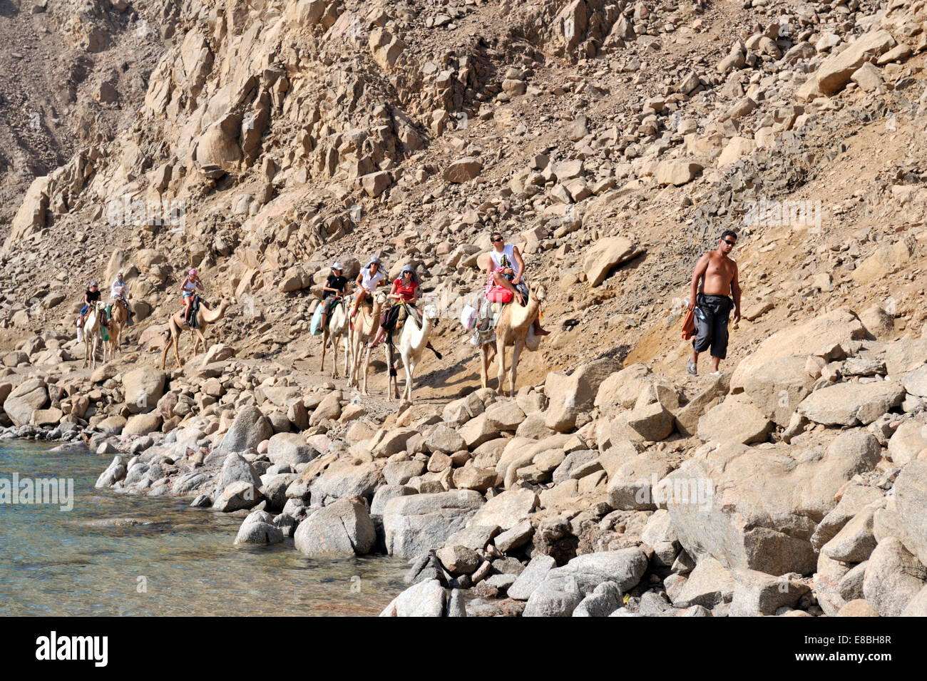 Sinai mountains meet the Gulf of Aqaba tourists on Bedouin camel trek north from Dahab to Ras Malah in southern - Stock Image