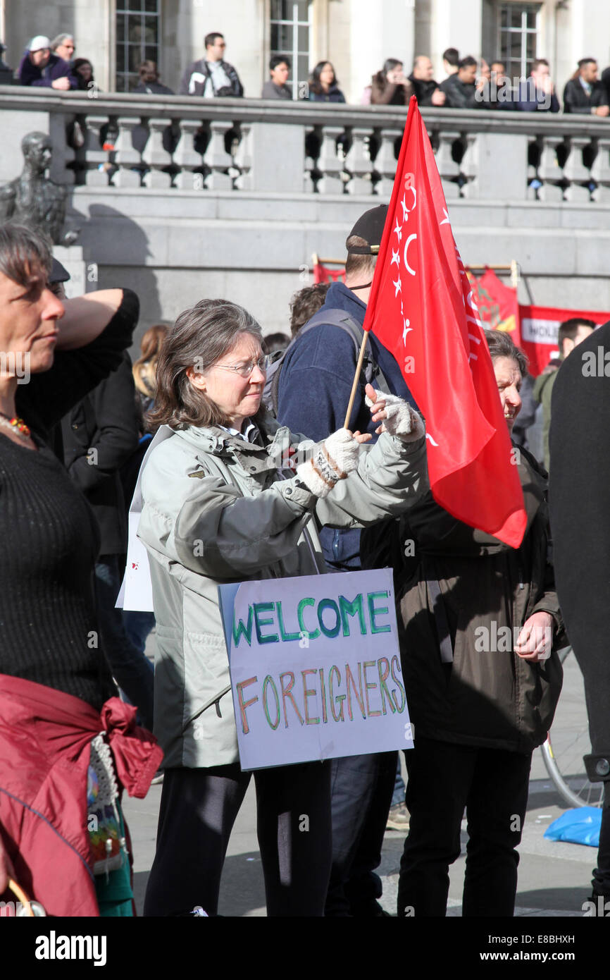 "A woman holds a sign saying ""Welcome Foreigners"" during a rally in London's Trafalgar Square to mark UN Anti-Racism Stock Photo"