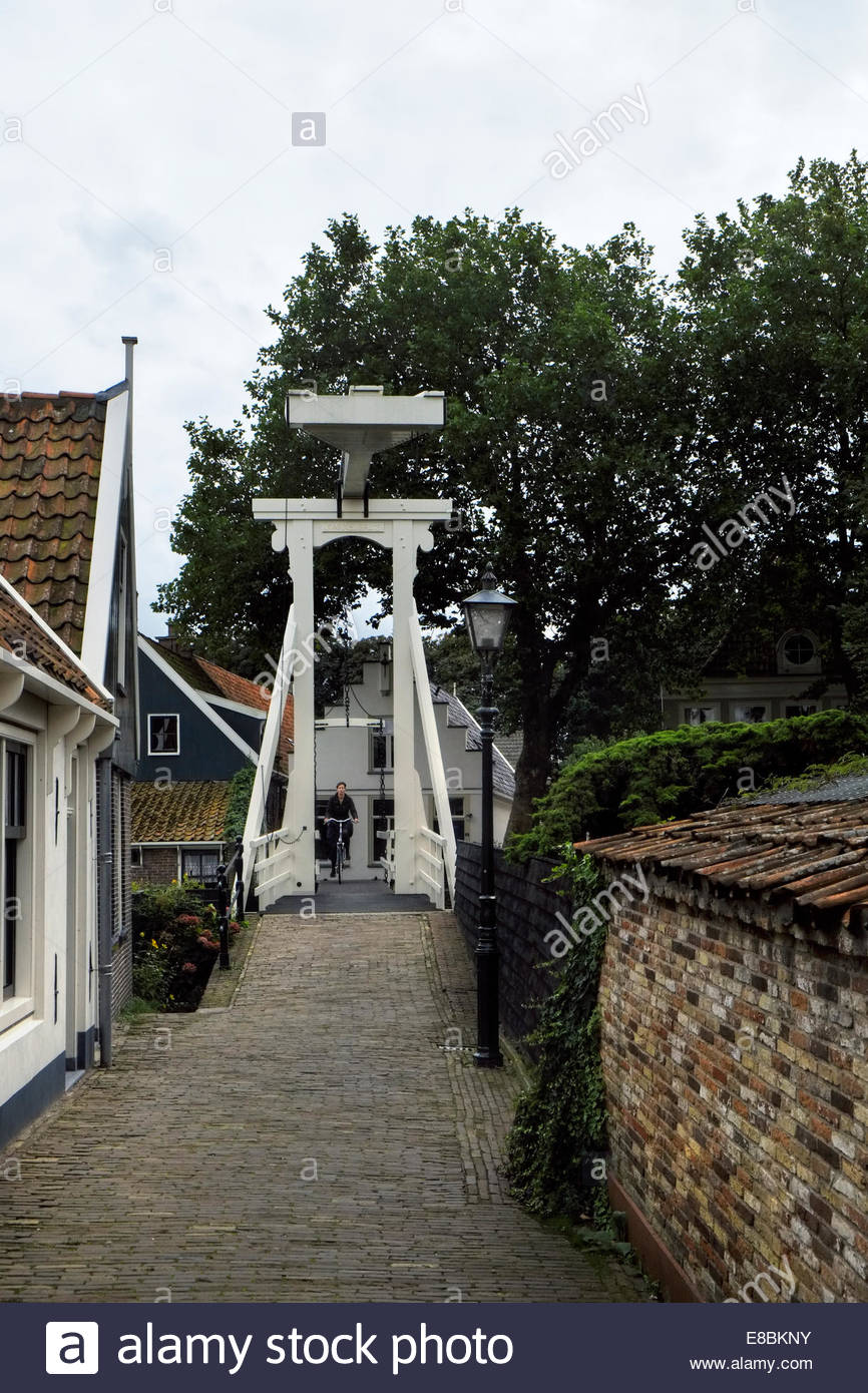 A person cycles across a draw bridge onto the Kwakelsteeg alleyway in the old town area of Edam, North Holland, - Stock Image