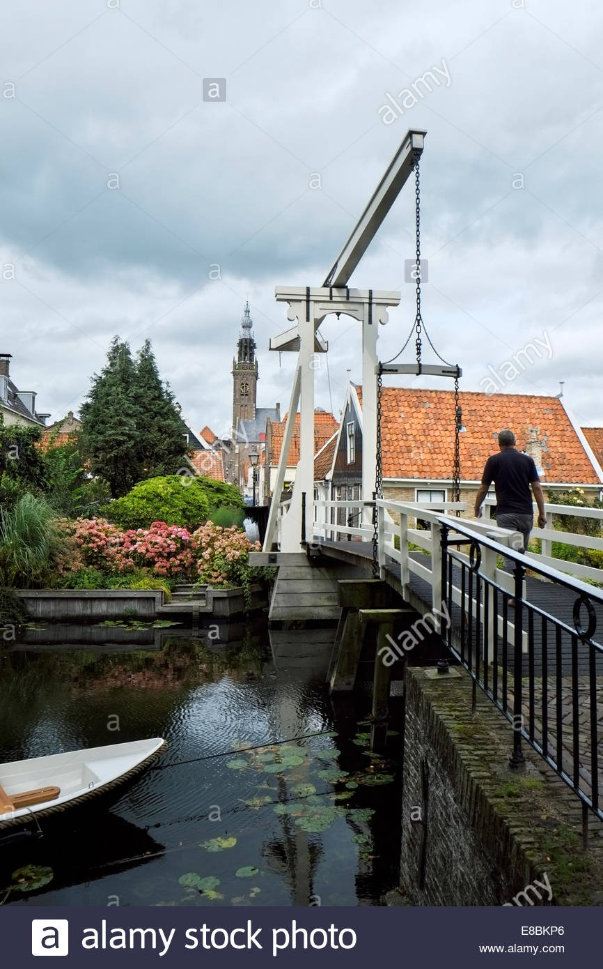 A man walks across the Kwakelsteeg bridge in old town Edam, North Holland, the steeple of the Kleine Kerk seen in Stock Photo