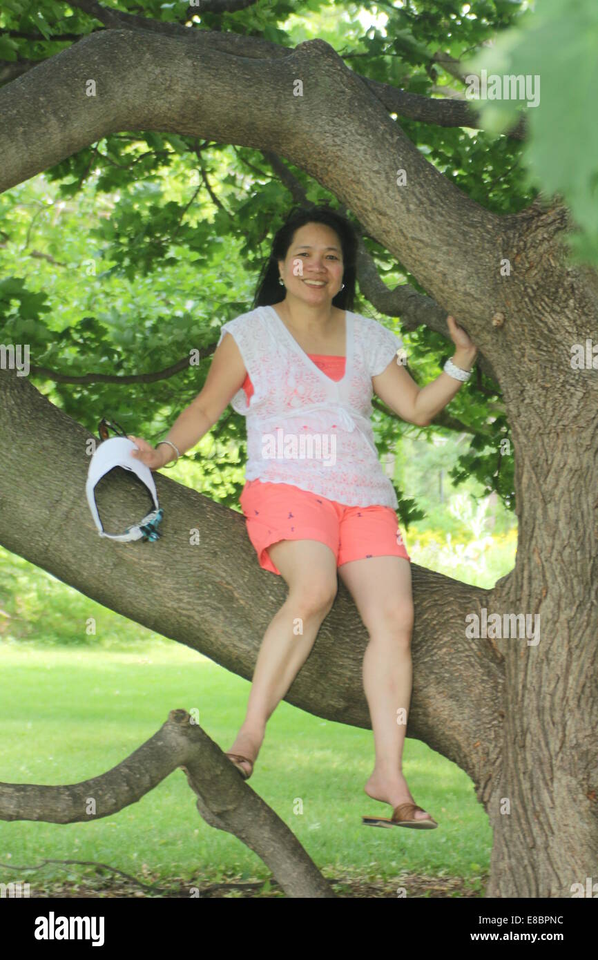mature asian woman wearing shorts, sitting on a large branch of a