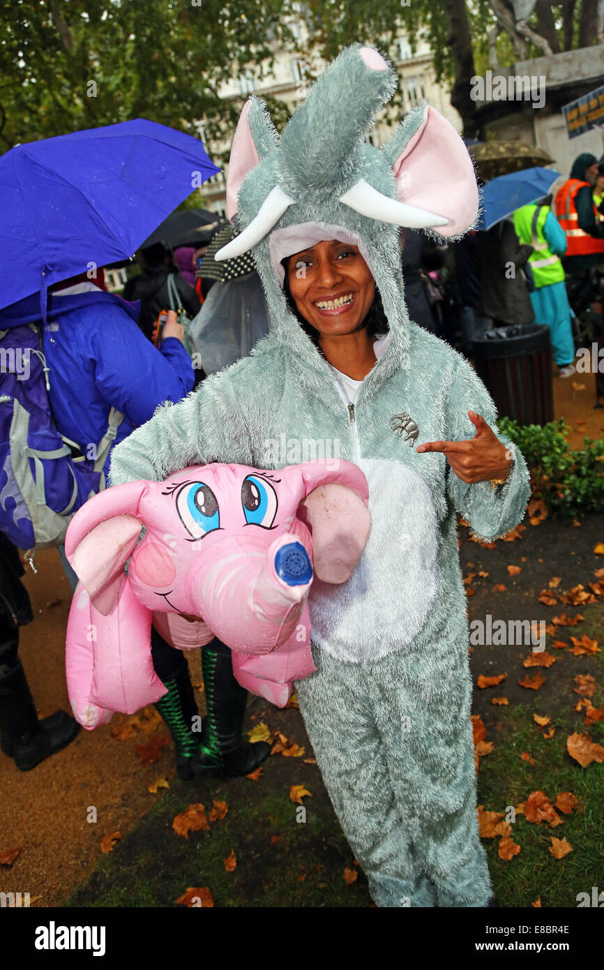 London, UK. 4th October 2014. Marchers dressed as an elephant with and inflatable pink elephant at the Global March - Stock Image