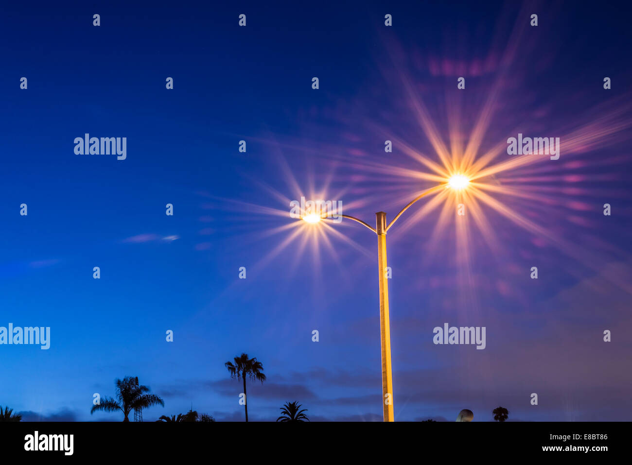 Light post in a parking lot viewed at night. - Stock Image
