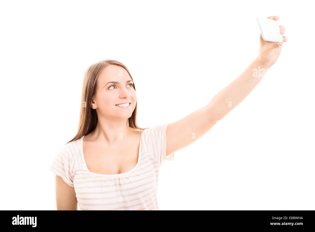 Young girl making a photograph of herself isolated on white background - Stock Image