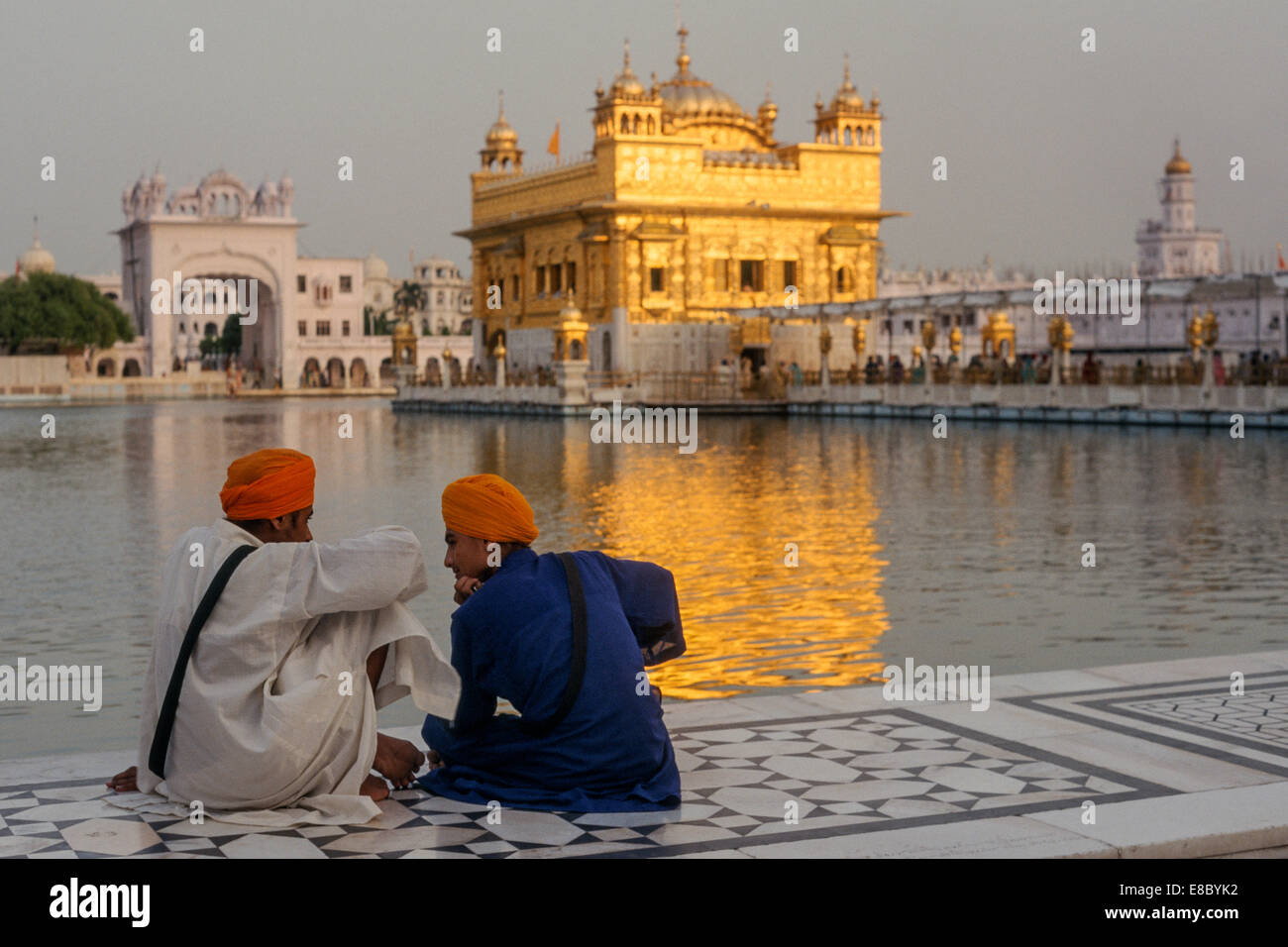 Two young men sitting opposite the Harmandir Sahib, or Golden Temple, one of the most revered sites for Sikhs, Amritsar, - Stock Image