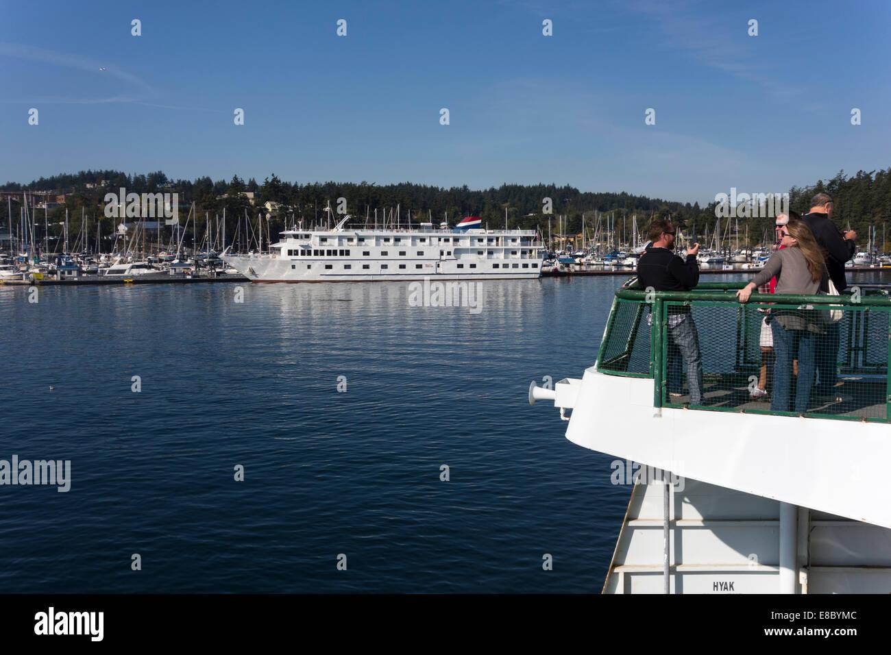 Washington State ferry approaching Roche Harbor, San Juan Islands, USA, with American Spirit cruise ship docked, - Stock Image