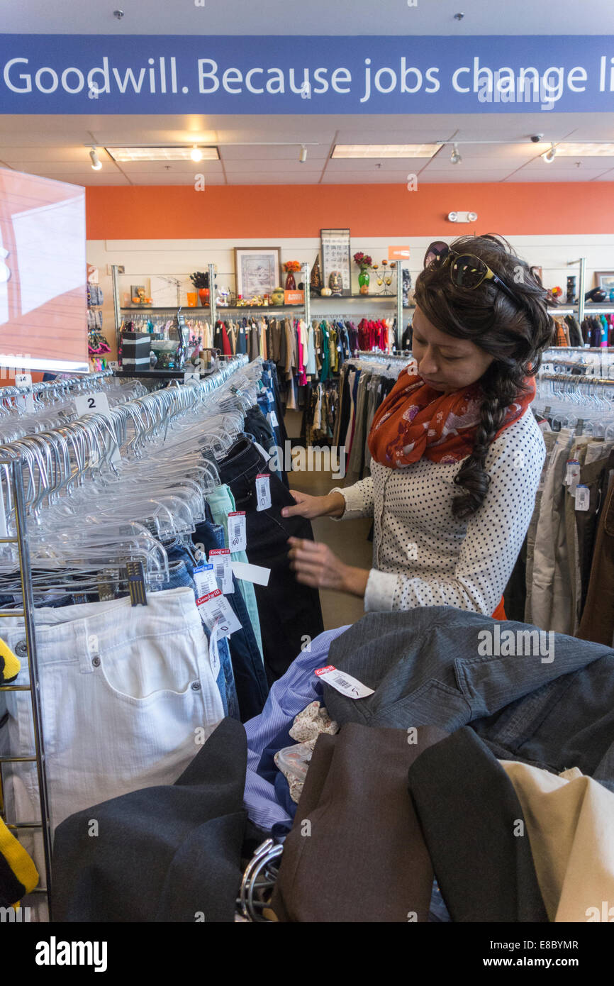 young woman clothes shopping at Goodwill store, Seattle, USA - Stock Image
