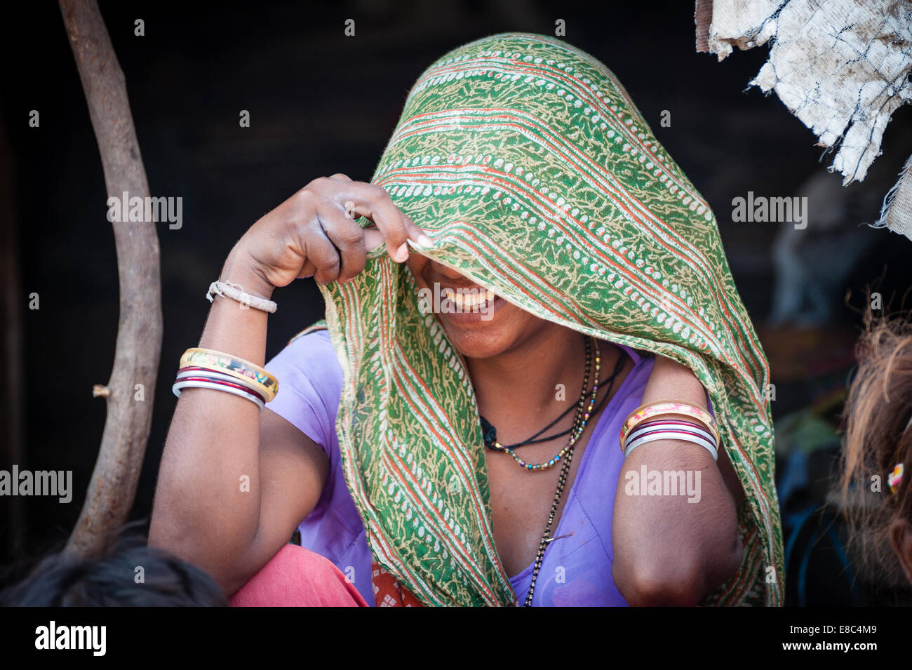 A shy Indian woman is smiling under sharee - Stock Image