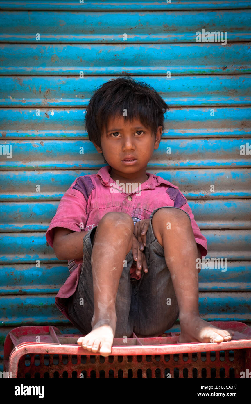 Lonely poor innocent Indian child sitting on a box on the roadside - Stock Image