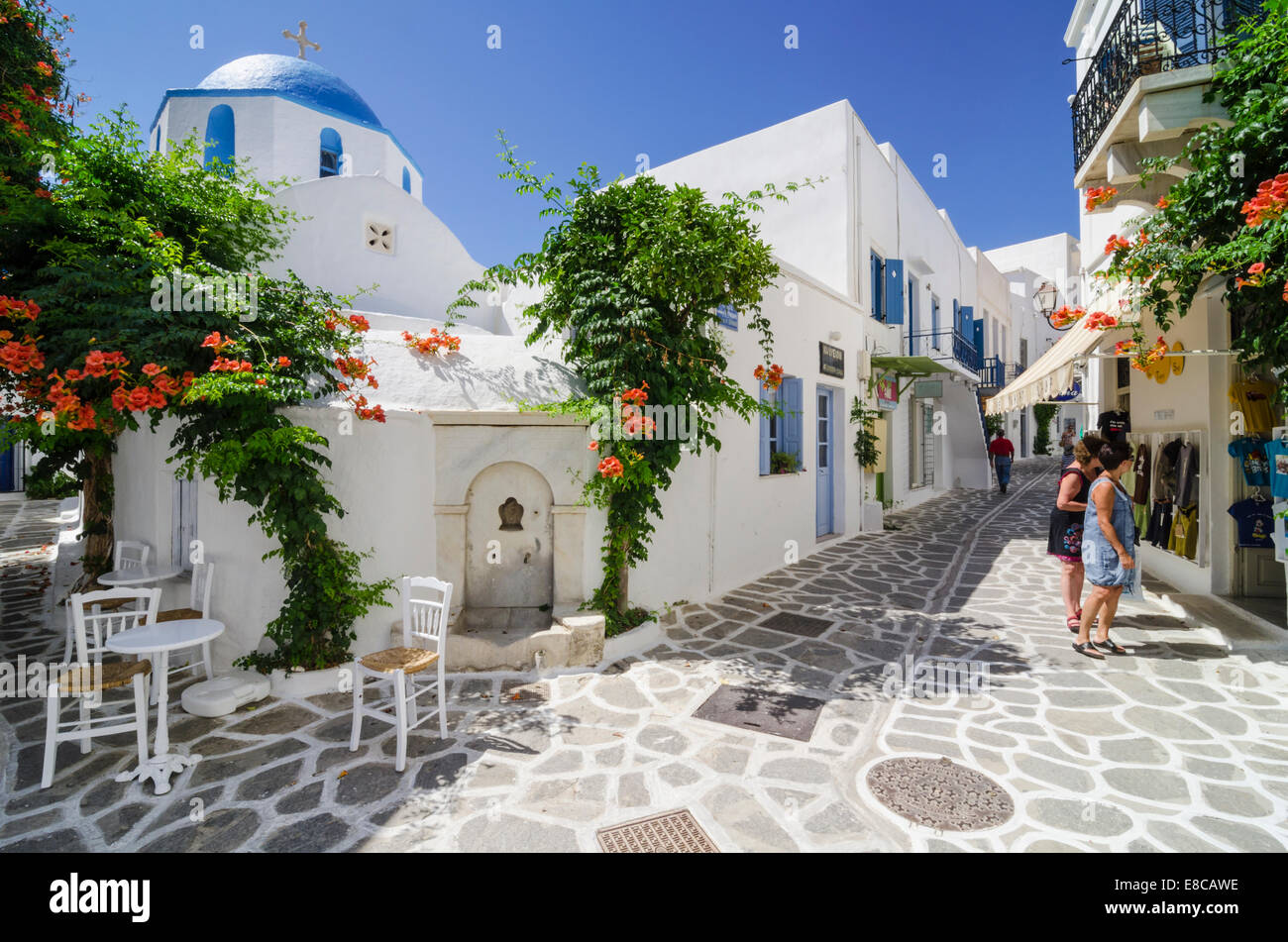 Greek water fountain and blue domed church in the whitewashed streets of Parikia Town on the island of Paros, Cyclades, Stock Photo