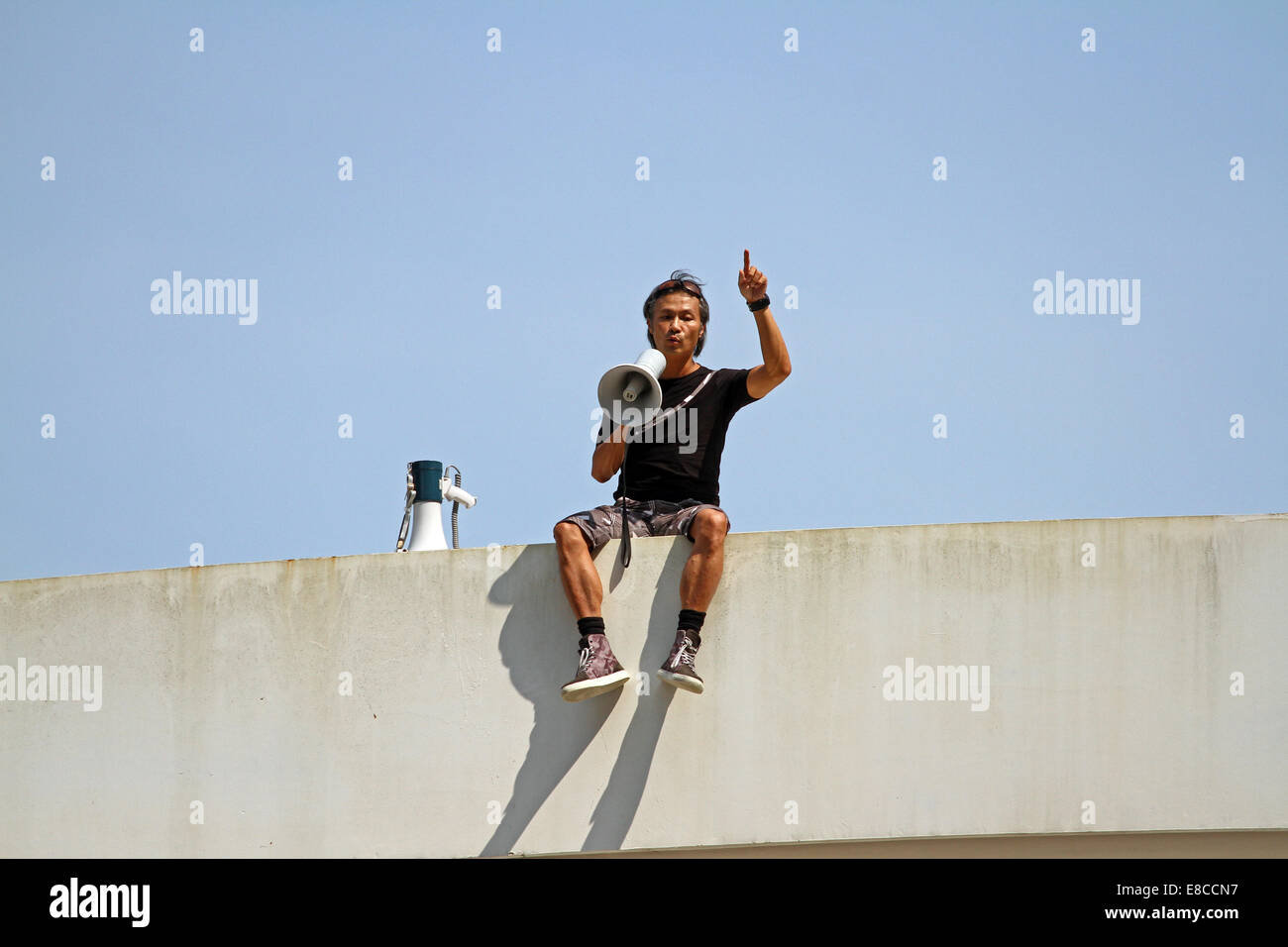 A man threatens to throw himself off a bridge during the pro-democracy protests in Hong Kong, October 2014 Stock Photo