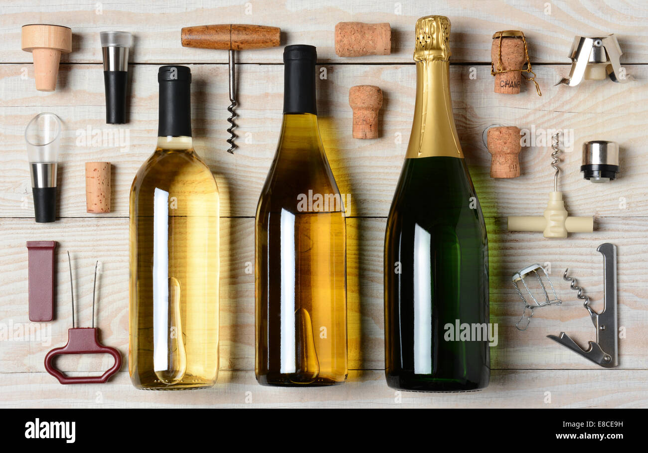 High angle shot of Wine and Champagne bottles surrounded by accessories such as corkscrews, stoppers, pourers and - Stock Image
