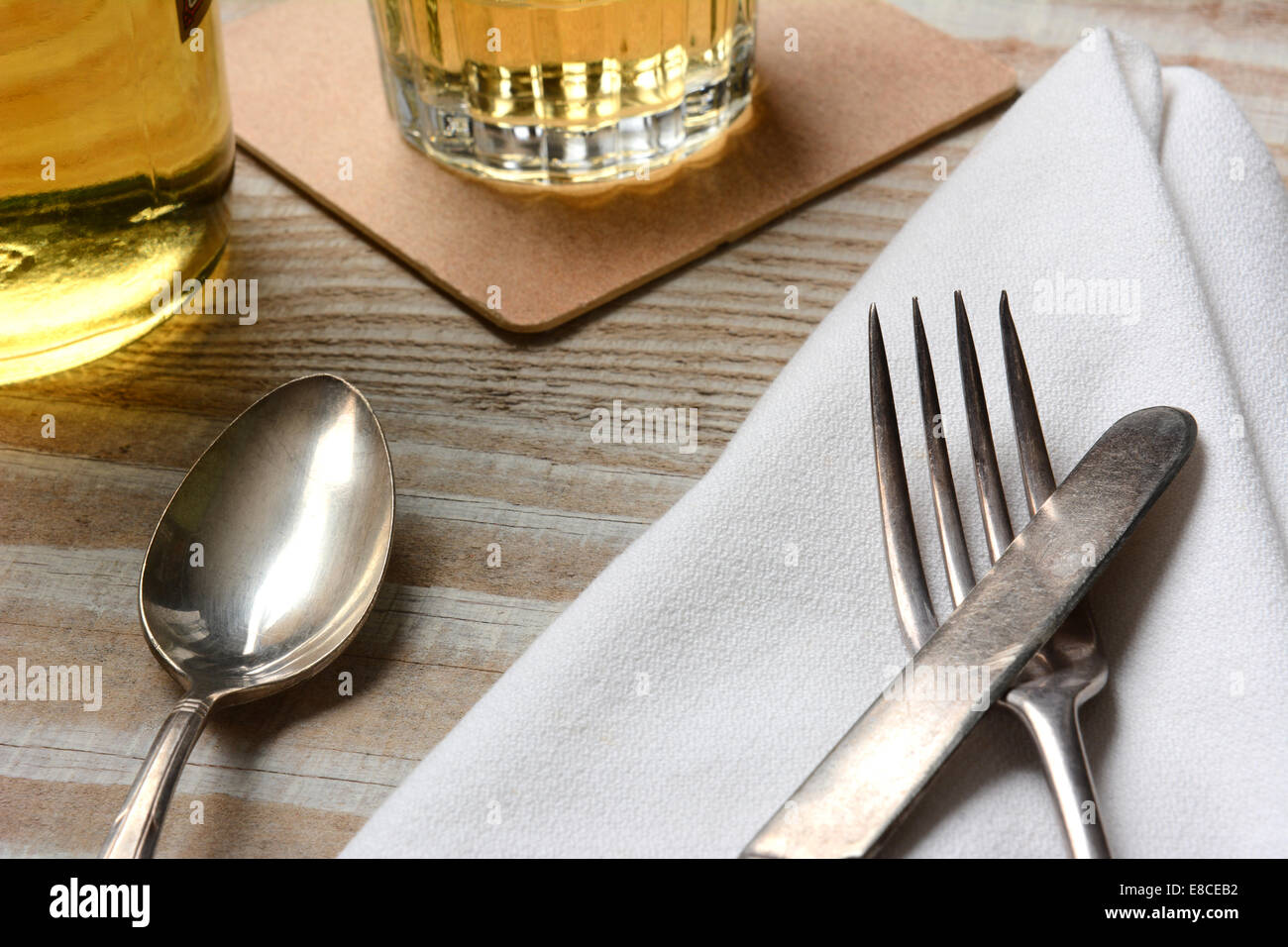 Closeup of a table setting. Old silverware napkin and drinks on a white wood table. Horizontal format & Closeup of a table setting. Old silverware napkin and drinks on a ...