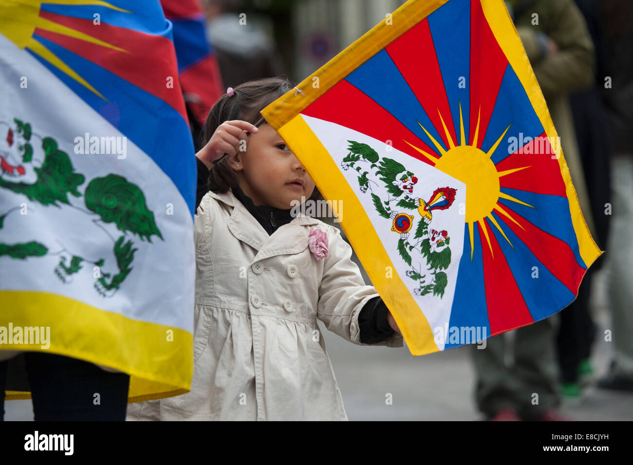 A little Tibetan girl is handling her flag at a protest rally of exile Tibetans in Bern, Switzerland - Stock Image