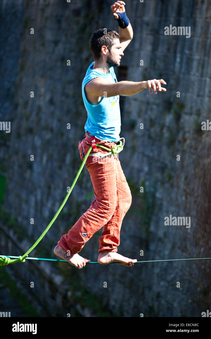 Slacklining is a practice in balance that typically uses nylon or polyester webbing tension between two anchor points. - Stock Image